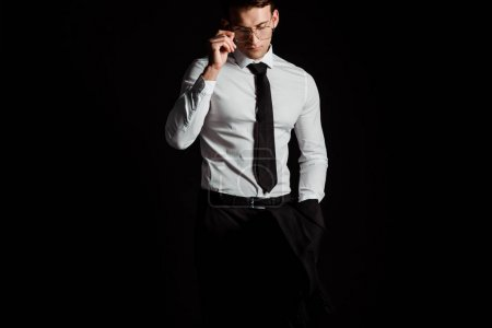 handsome businessman touching glasses isolated on black