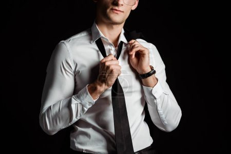 cropped view of businessman taking off tie isolated on black