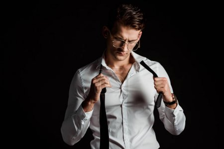 gutaussehender Geschäftsmann mit Brille, Krawatte abnehmend, auf Schwarz