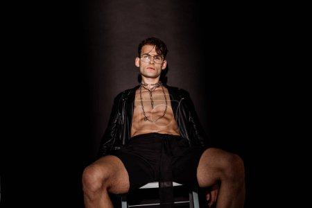 Photo pour Jeune homme sexy et brutal dans des lunettes et la veste en cuir s'asseyant sur le noir - image libre de droit