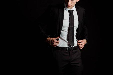 Photo pour Vue recadrée de l'homme touchant costume isolé sur noir - image libre de droit