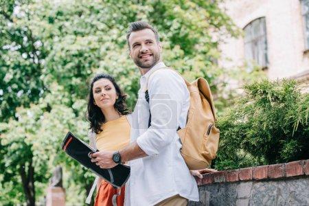 Photo pour Heureux barbu homme tenant carte près attrayant femme - image libre de droit