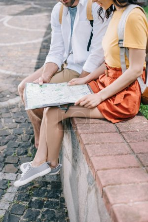 cropped view of man and woman sitting with map