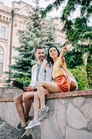 Foto de Mujer atractiva señalando con el dedo y sentado cerca de hombre feliz con mapa - Imagen libre de derechos