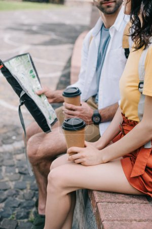 cropped view of bearded man with paper cup and map sitting near girl