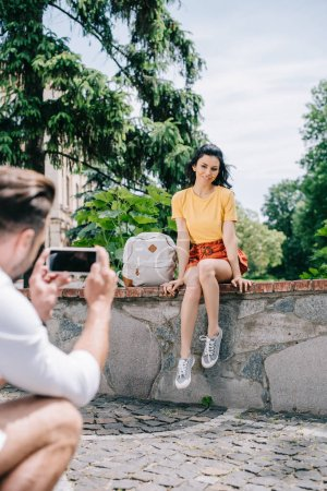 Photo for Cropped view of man holding smartphone with blank screen near attractive woman - Royalty Free Image