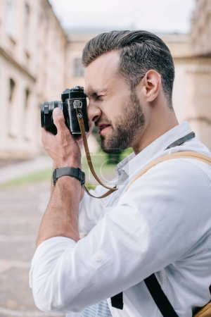 Photo for Side view of bearded man taking photo on digital camera - Royalty Free Image