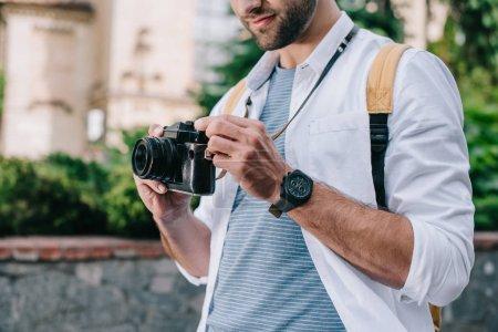 Photo pour Vue recadrée de l'homme barbu retenant l'appareil-photo numérique - image libre de droit