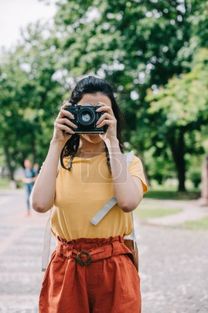 Photo for Woman covering face while taking photo on digital camera - Royalty Free Image