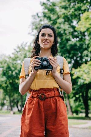 Photo pour Jeune femme heureux retenant l'appareil-photo numérique à l'extérieur - image libre de droit