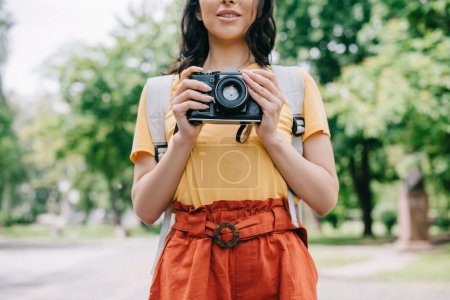 Photo for Cropped view of young woman holding digital camera outside - Royalty Free Image