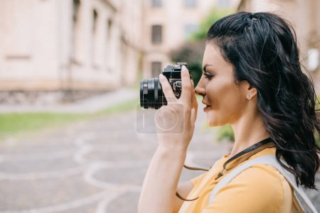 Photo for Side view of attractive girl holding digital camera while taking photo - Royalty Free Image