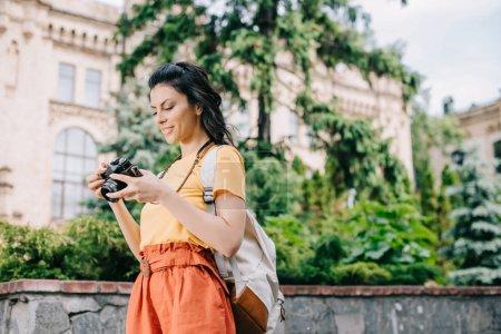 Photo pour Fille tenant une caméra numérique près d'un bâtiment et d'arbres - image libre de droit