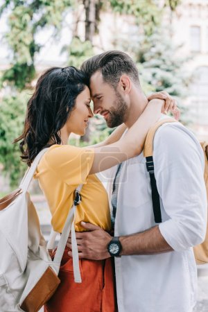 Attractive woman hugging bearded and happy boyfriend