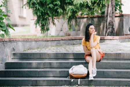attraktive Frau sitzt neben Rucksack auf Treppe
