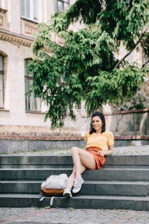 Photo for Attractive young woman sitting near backpack on stairs - Royalty Free Image