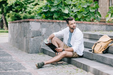 beau voyageur barbu assis sur les escaliers et regardant la carte