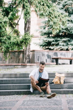 Photo for Handsome bearded man sitting on stairs and looking at map near trees - Royalty Free Image