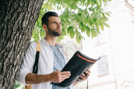 Photo for Low angle view of bearded man holding map near tree - Royalty Free Image