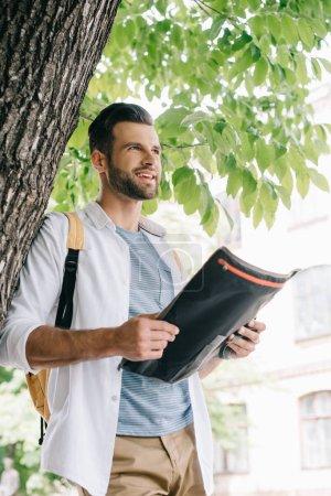 Photo pour Voyageur barbu heureux retenant la carte près de l'arbre - image libre de droit