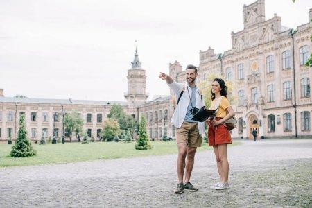 Photo pour Bel homme pointant du doigt tout en tenant la carte près de fille attrayante et campus universitaire - image libre de droit