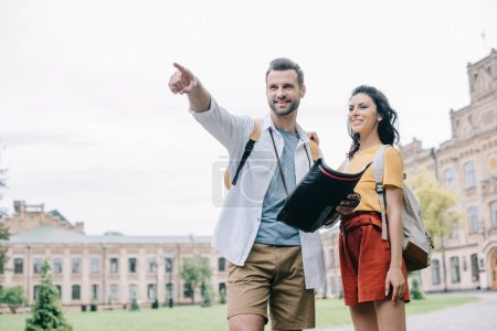 glücklicher Mann zeigt mit dem Finger, während er Landkarte in der Nähe von Frau hält