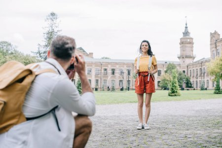 Photo for Selective focus of happy woman standing near building and man taking photo - Royalty Free Image