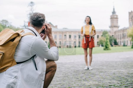 Photo for Selective focus of man taking photo of happy woman standing near building - Royalty Free Image