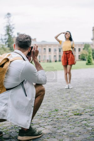 Photo for Selective focus of man taking photo of young woman standing near building - Royalty Free Image