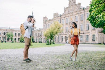 bearded man taking photo of attractive girl near university