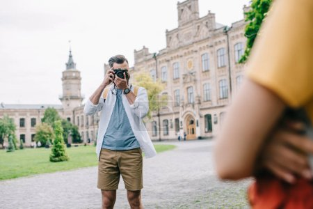 Photo for Selective focus of man covering face while taking photo of woman near university - Royalty Free Image