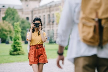Photo for Selective focus of woman covering face while taking photo of man near university - Royalty Free Image