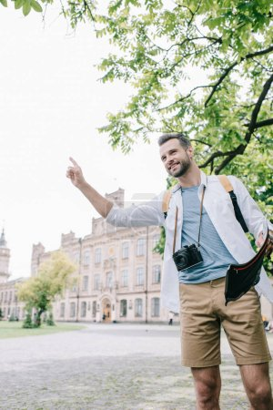 Photo for Happy man holding with finger while holding map - Royalty Free Image