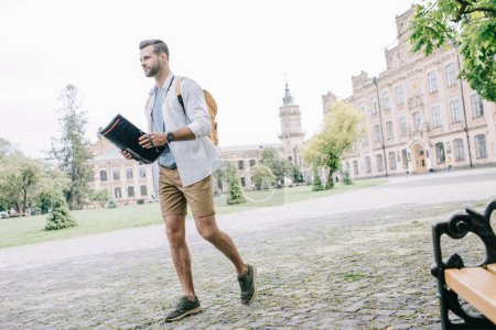 Photo pour Handsome man walking in city with backpack and map - image libre de droit