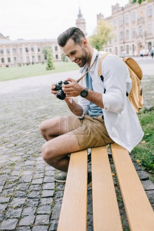selective focus of happy man looking at digital camera while sitting on bench