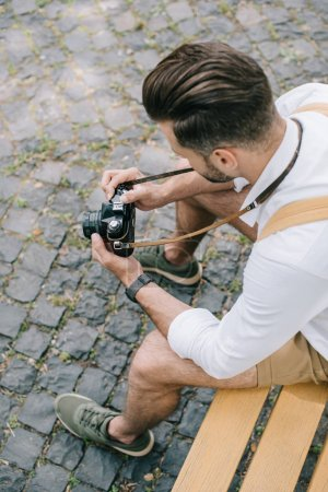 Photo for Overhead view of bearded man holding digital camera in hands - Royalty Free Image