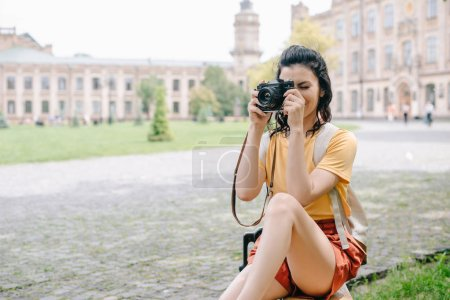 Photo for Young woman covering face while taking photo near university - Royalty Free Image