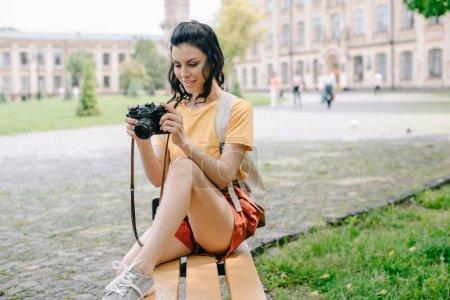 Photo pour Une jeune femme attirante regarde un appareil photo numérique alors qu'elle est assise sur un banc près de l'université - image libre de droit
