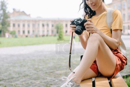 Photo pour Vue recadrée d'une jeune femme tenant un appareil photo numérique alors qu'elle était assise sur un banc près de l'université - image libre de droit