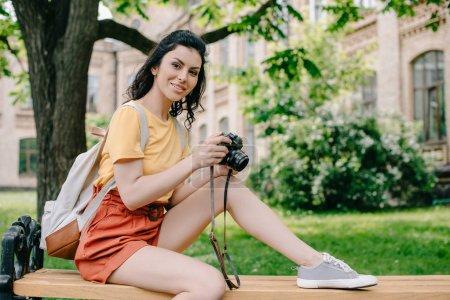 Photo pour Joyeuse fille tenant appareil photo numérique tout en étant assis sur le banc près de l'université - image libre de droit