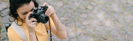 Photo for Panoramic shot of woman taking photo on digital camera - Royalty Free Image