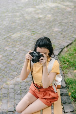 Photo for Overhead view of girl taking photo on digital camera outside - Royalty Free Image