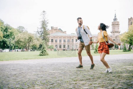 Photo for Cheerful bearded man and woman holding hands while running near building - Royalty Free Image