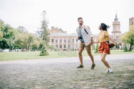 Foto de Alegre hombre y mujer cojinados con las manos mientras corren cerca de la construcción. - Imagen libre de derechos