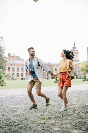 Photo pour Homme et femme barbus heureux se tenant la main en courant près d'un bâtiment - image libre de droit