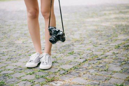 Photo pour Vue recadrée de fille restant avec l'appareil-photo numérique à l'extérieur - image libre de droit
