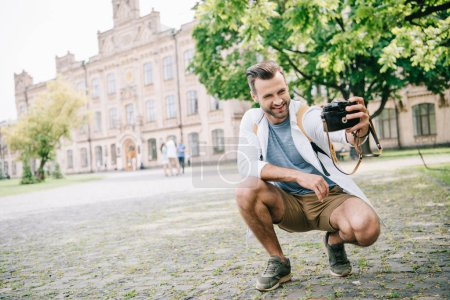 Photo for Cheerful bearded man taking selfie on digital camera near building - Royalty Free Image