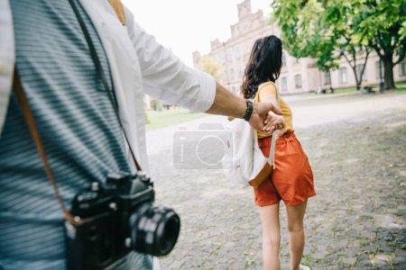 Photo pour Vue recadrée de l'homme tenant la main avec fille marchant près de l'université - image libre de droit