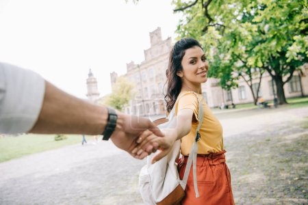 Photo for Cropped view of man holding hands with attractive girl walking near university - Royalty Free Image