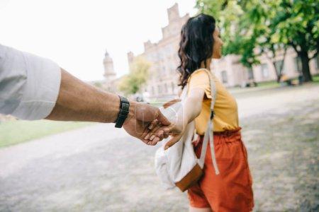 Photo pour Vue recadrée de l'homme tenant la main avec une femme marchant près de l'université - image libre de droit